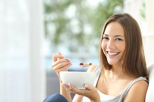Woman eating cornflakes at home.jpg
