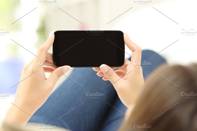Woman watching media in a smart phone.jpg - Technology