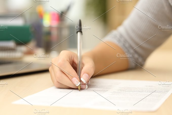 Woman hand writing or signing in a document.jpg - Business