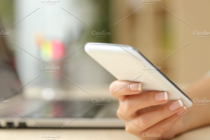 Woman hand using a white smart phone.jpg - Technology