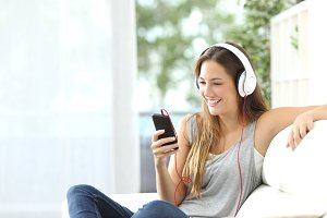 Happy girl listening to music from mobile phone.jpg