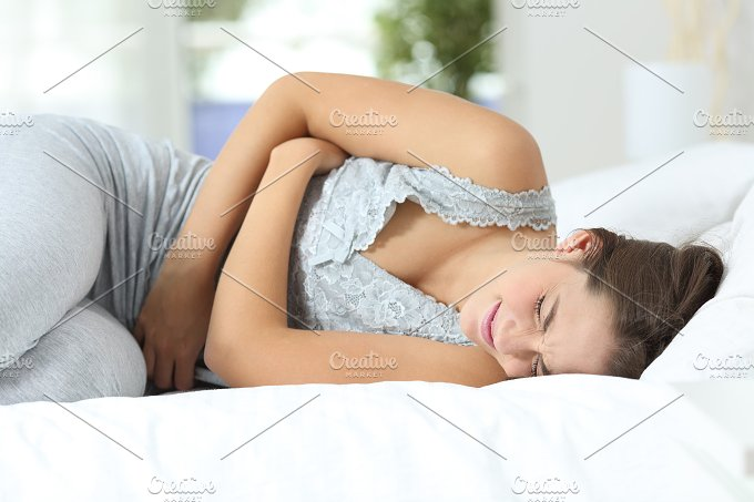 Girl suffering menstrual pains on the bed.jpg - Health
