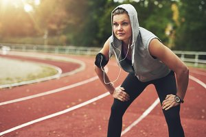 Woman exercising in hoodie at track