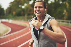 Smiling woman running at track