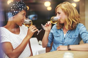Two women drinking wine at cafe