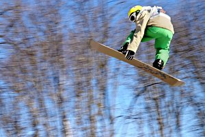 Colorful snowboarder jumps