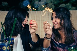 Happy women couple holding sparklers