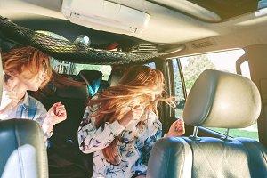 Women dancing and having fun in car