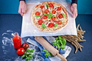 Closeup hand of baker making pizza a