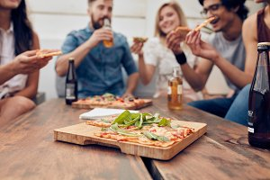 Pizza on table with friends enjoying