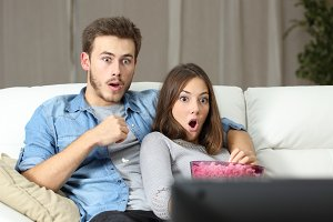 Amazed couple watching tv at home.jpg