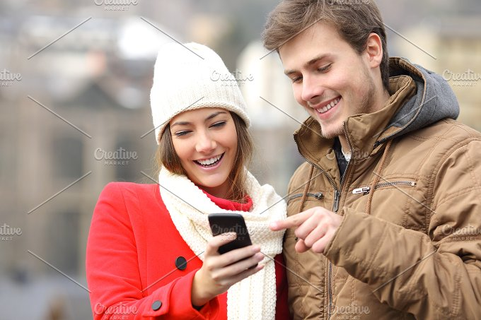 Couple consulting a smart phone in winter.jpg - Technology