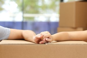 Couple holding hands over a box moving home.jpg