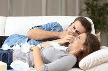 Ill couple sneezing in tissue flu concept.jpg
