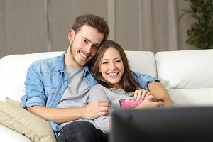Happy couple watching movie on tv.jpg