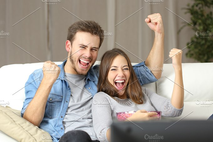 Euphoric couple watching tv at home.jpg - Technology