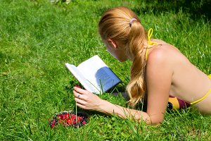 girl  reads book on the green grass