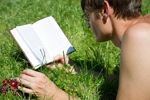 Man reads a book on the green grass