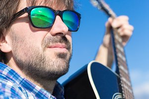 Bearded man in sunglasses playing