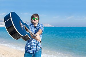 bearded man in sunglasses and guitar