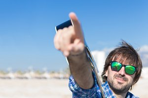 Bearded man in sunglasses pointing