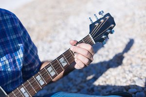 Closeup of man hand playing guitar