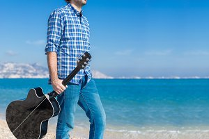 Man with guitar walking along beach
