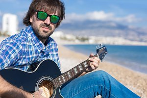Portrait of bearded man plays guitar