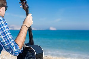 Man with guitar sitting on coast
