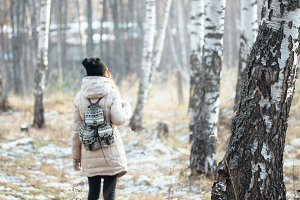 girl with backpack in winter forest