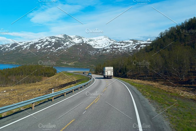 Truck on the grey asphalt road to Norwegian mountains in clear day.jpg - Photos