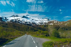 Car on the grey road to Norvegian mountains in sunny clear day.jpg