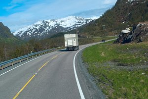 Truck on the grey road to Norwegian mountains in clear day.jpg