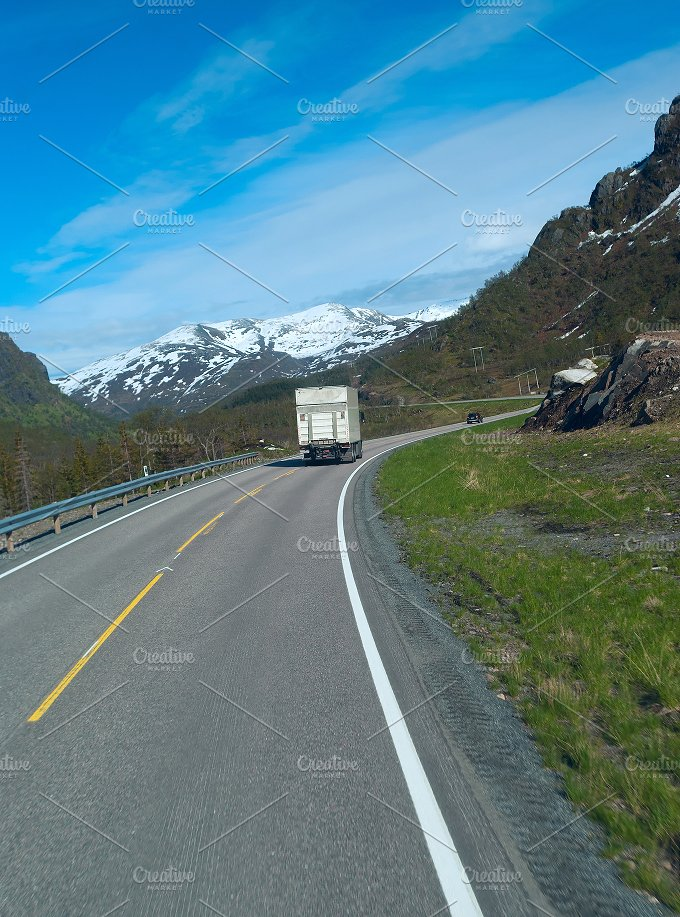 Truck on the grey road to Norwegian mountains in clear day.jpg - Photos