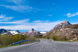 Grey road to Norvegian mountains in sunny summer day.jpg
