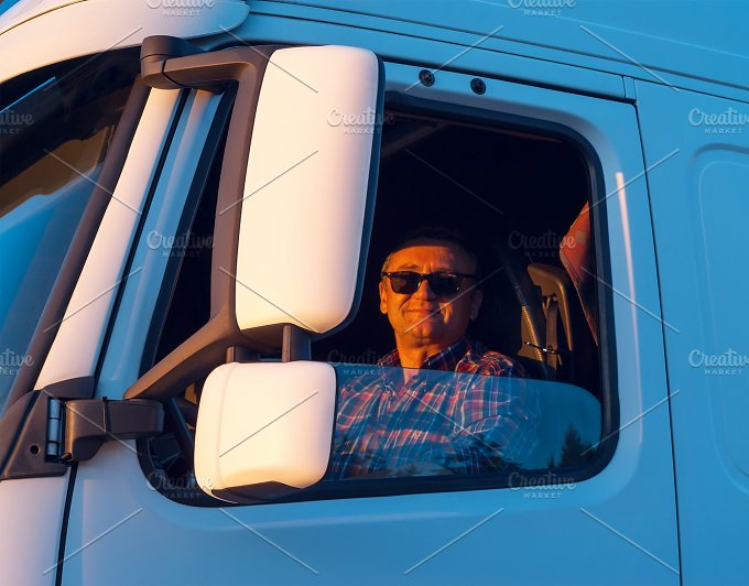 Driver in the cabin of him white truck.jpg - Transportation