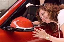 woman looks in mirror of red car.jpg