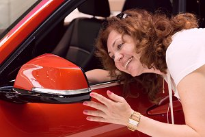 woman looks in mirror of red car.jpg