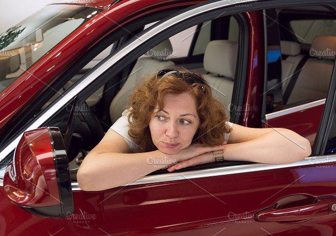 Woman looks in a car mirror.jpg - People