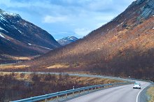 Grey road in Norvegian green mountains.jpg