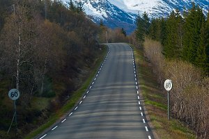 Grey asphalt road in Norvegian green mountains.jpg