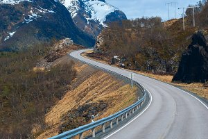 Grey road in Norvegian snowbound mountains.jpg