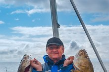 Fisherman in blue overalls on a boat with codfish.jpg