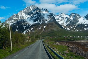 Asphalt road to Norwegian mountains in sunny clear day.jpg