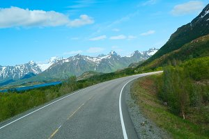 Asphalt road to Norvegian mountains in summer clear day.jpg