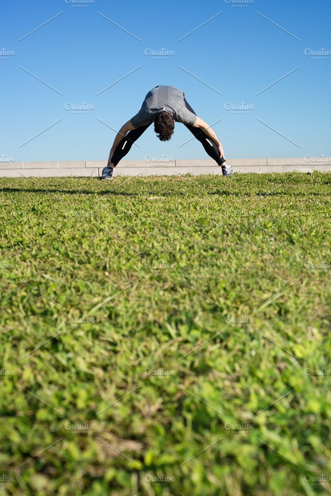 Man doing strechings before running space for text down.jpg - Sports