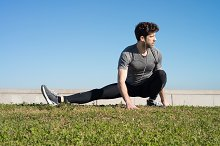 man stretches leg in the ground in the grass.jpg