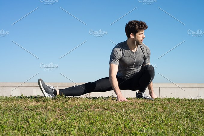 man stretches leg in the ground in the grass.jpg - Sports