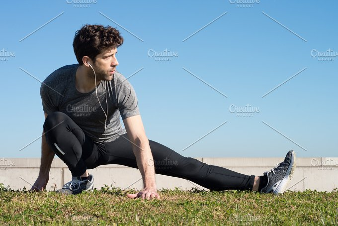 man stretches leg in the ground watching to right.jpg - Sports