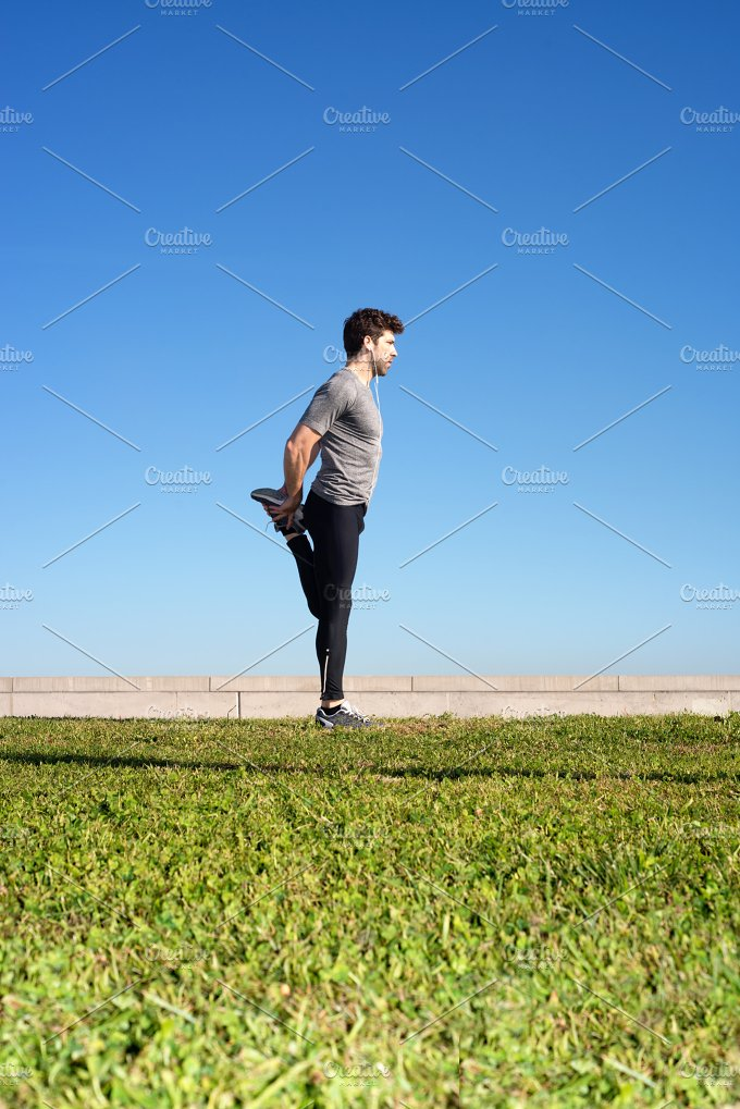 man stretches the leg before running space for text down.jpg - Sports